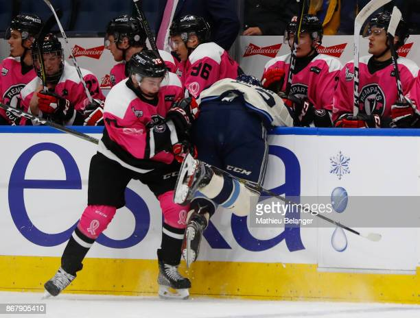 Pierrick Dude of the Quebec Remparts hits Alexandre Joncas of the Sherbrooke Phoenix during the second period of their QMJHL hockey game at the...