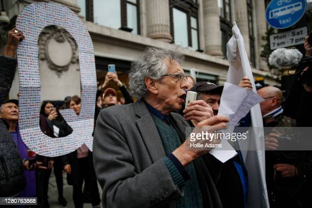 Piers Corbyn speaks to demonstrators as a man holds up a QAnon sign behind him during a StandUpX March for Freedom protest on October 17, 2020 in...