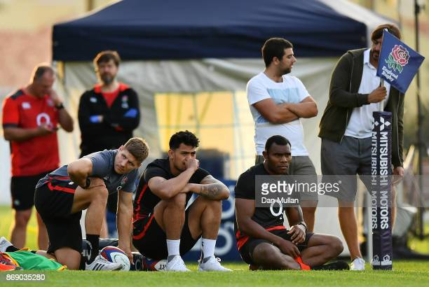 Piers Francis Denny Solomona and Semesa Rokoduguni of England watch from the touchline during a training session at Browns Sport Leisure Club on...