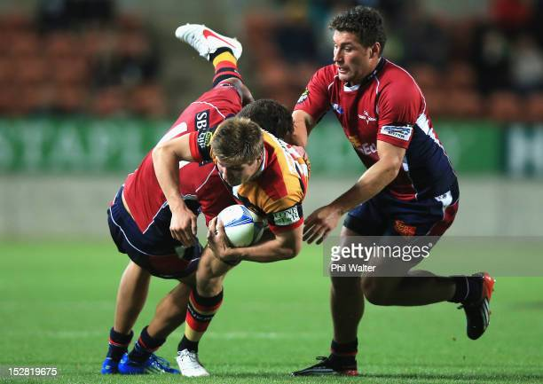 Piers Francis of Waikato is tackled by Peter Betham and Kieron Fonotia of Tasman during the round 11 ITM Cup match between Waikato and Tasman at...
