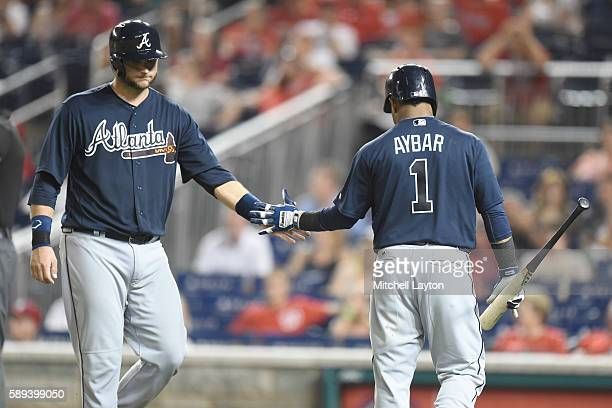 J Pierzynski of the Atlanta Braves celebrates scoring a run with Erick Aybar on a Edder Incarte single in the ninth inning during a baseball game...