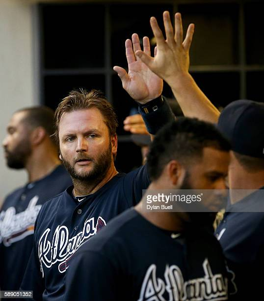 J Pierzynski of the Atlanta Braves is congratulated by teammates after scoring a run in the third inning against the Milwaukee Brewers at Miller Park...