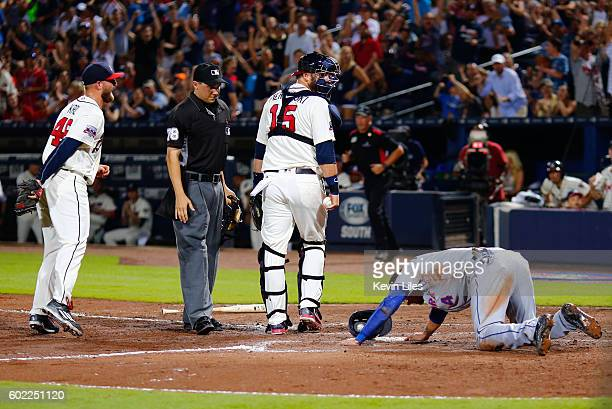 J Pierzynski of the Atlanta Braves looks at Wilmer Flores of the New York Mets after Flores is out at home in a collision during the eighth inning at...
