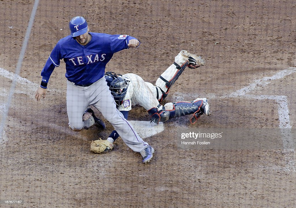 A.J. Pierzynski #12 of the Texas Rangers is safe as Ryan Doumit #9 of the Minnesota Twins defends home plate during the ninth inning of the game on April 27, 2013 at Target Field in Minneapolis, Minnesota. The Twins defeated the Rangers 7-2.