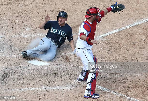 J Pierzynski of the Texas Rangers looks on as Kyle Seager of the Seattle Mariners scores on a RBI single by Dustin Ackley at Rangers Ballpark in...