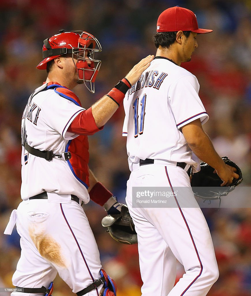 A.J. Pierzynski #12 of the Texas Rangers talks with Yu Darvish #11 on the mound against the Minnesota Twins in the 7th inning at Rangers Ballpark in Arlington on August 30, 2013 in Arlington, Texas.