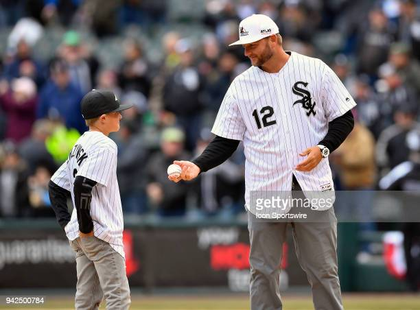J Pierzynski offers the ball to his son to throw the ceremonial first pitch before the Opening Day home game between the Chicago White Sox and the...
