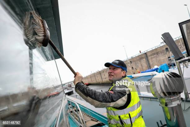 Piet van Meel, captain of the Tiamo cargo vessel, cleans the window of the bridge as he waits on the Scheldt-Rhine Canal lock system near Bruinisse,...
