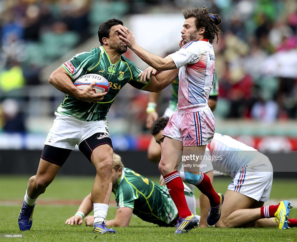 Pieter Engelbrecht of South Africa hands off the tackle of Jean Baptiste Gobelet of France during the Marriottt London Sevens - Day One at Twickenham on May 11, 2013 in London, England.