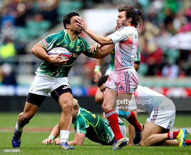 Pieter Engelbrecht of South Africa hands off the tackle of Jean Baptiste Gobelet of France during the Marriottt London Sevens Day One at Twickenham...