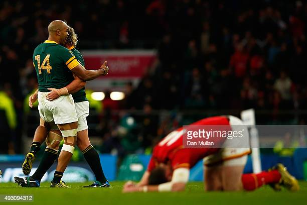 Pietersen of South Africa and Jannie Du Plessis of South Africa celebrate as Alex Cuthbert of Wales kneels dejected on the pitch at the final whistle...