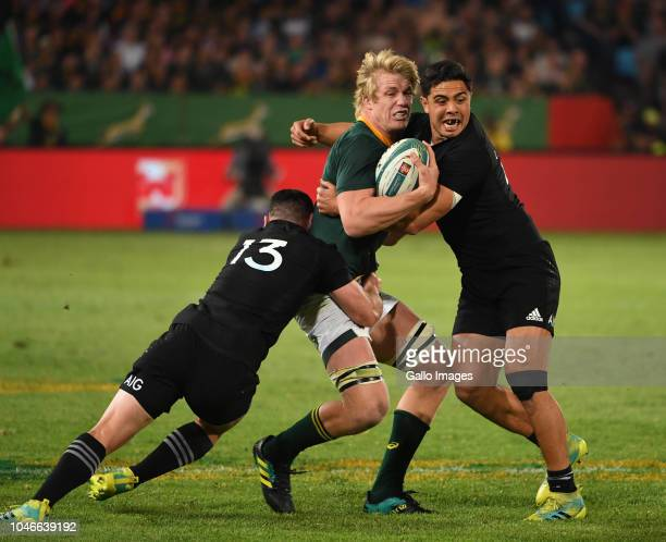 PieterSteph du Toit of the Springboks tackled by Anton LienertBrown and Ryan Crotty of New Zealand during the Rugby Championship match between South...