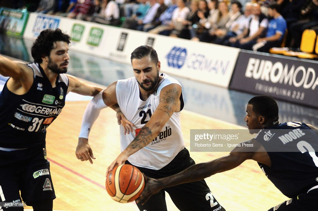 Pietro Aradori of Segafredo competes with Michele Vitali (L) and Lee Moore (R) of Germani during the match between Virtus Segafredo Bologna and Leonessa Germani Brescia of the Roberto Ferrari Basketball Trophy at PalaGeorge on September 23, 2017 in Montichiari, Italy.