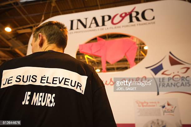 A pig breeder wearing a vest with the inscription 'I am a breeder and I am dying' is pictured on the opening day of the 'Salon de l'Agriculture' in...