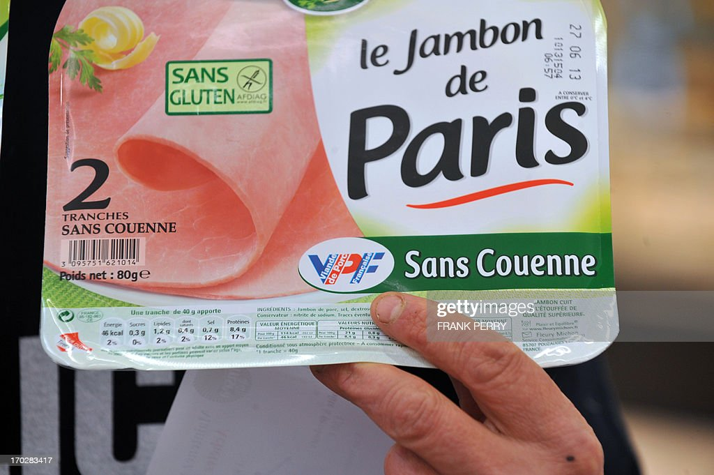 A pig farmer, member of the French FNSEA union, shows ham with the VPF label (French origin) in a Leclerc supermarket during a demonstration against meat from foreign countries on June 10, 2013 in Saint-Herblain, near Nantes.