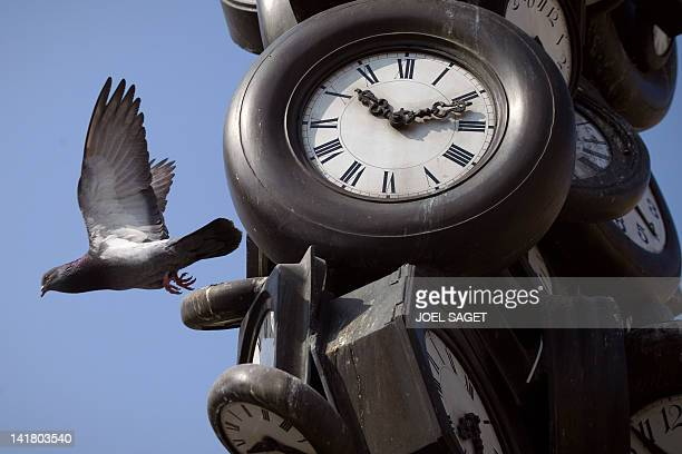 A pigeon flies passed clocks on March 24 2012 in Paris Europe moves to summer time at 0100 GMT on March 25 when clocks go forward an hour AFP...