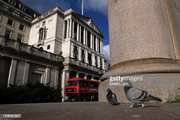 Pigeons are pictured in a general view of the Bank of England in the City of London on March 11 2020 Britain's government and the Bank of England on...