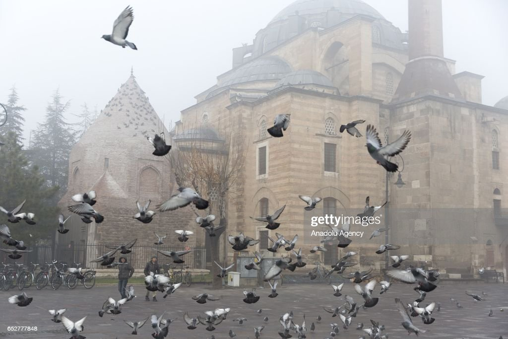 Pigeons fly around the Serafettin Mosque during foggy morning in Konya, Turkey on march 13, 2017.