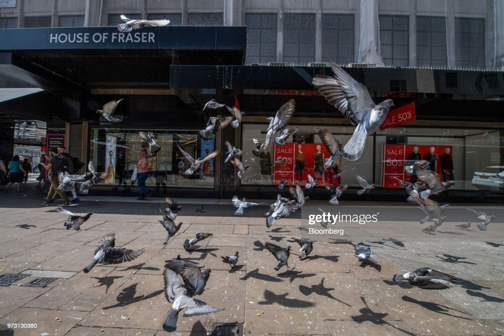 Pigeons fly in front of a House of Fraser store, one of the stores slated for closure, on Oxford Street, in central London, U.K., on Wednesday, June 13, 2018. U.K. department-store chain House of Fraser said it plans to shut more than half its outlets, putting 6,000 jobs at risk. Photographer: Chris J. Ratcliffe/Bloomberg via Getty Images
