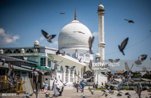 Pigeons fly in front the at Hazratbal shrine on the last Friday of the holy Islamic month of Ramadan on June 23 2017 in Srinagar the summer capital...