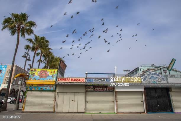 Pigeons fly over closed stores on the Boardwalk in Venice California on April 26 2020 Los Angeles County beaches are still off limits under the...
