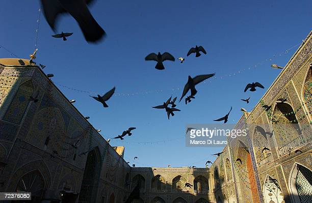 Pigeons fly over the shrine of Imam Ali at sunrise whilst Iraqis hold a prayer to celebrate Eid al-Adha on February 2, 2004 in Najaf, 180 km south of...