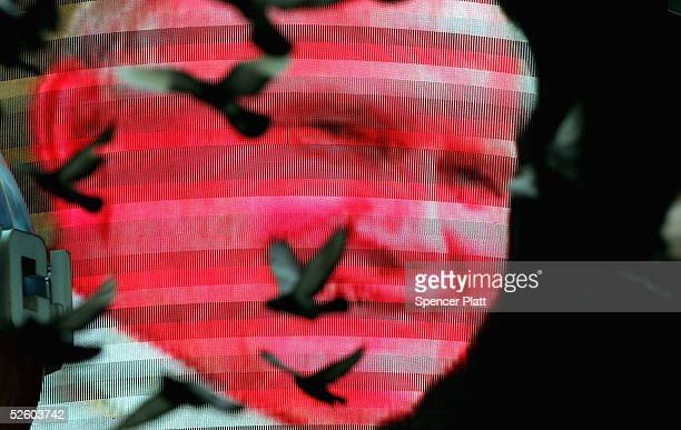 Pigeons fly past a video screen image depicting Pope John Paul II in Times Square April 8, 2005 in New York City. New Yorkers mourned the passing of...