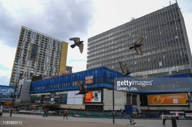 Pigeons fly past the Elephant Castle shopping centre and market are seen in south London on June 15 2019 Looming redevelopment projects have raised...