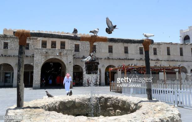 Pigeons linger around a fountain at Qatar's touristic Souq Waqif bazar in the capital Doha on May 17 as the country begins enforcing the world's...