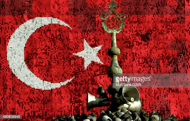 Pigeons sit on top of a minaret in front of a Turkish flag in Konak Square in Izmir western Turkey 18 December 2003 Mustafa Ozer