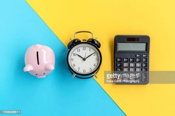 piggy bank, alarm clock and calculator - budget stock-fotos und bilder