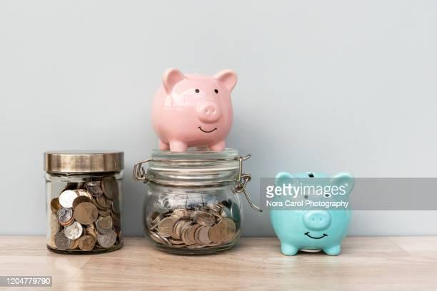 piggy bank and coin jar - devolver - fotografias e filmes do acervo