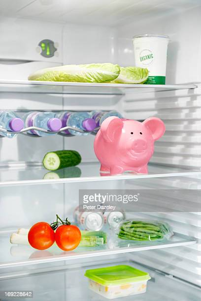 piggy bank and food in refrigerator - cost_of_living stock pictures, royalty-free photos & images
