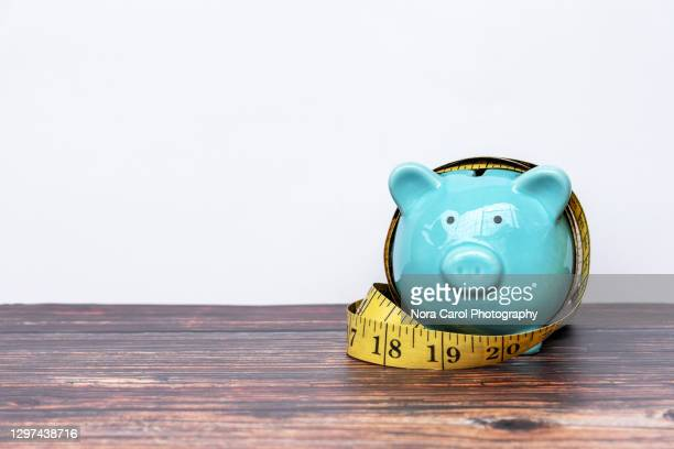 piggy bank and measuring tape - tighten stock pictures, royalty-free photos & images