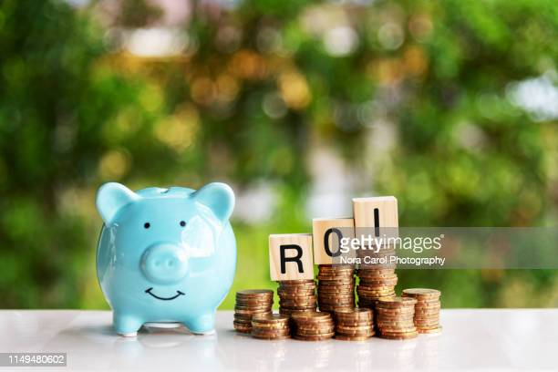 piggy bank and roi return of investment text on wood blocks on top of coins stack - return on investment stock pictures, royalty-free photos & images