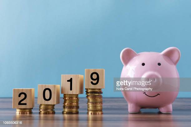 piggy bank and stack of coins with number 2019 - 2019 stock pictures, royalty-free photos & images