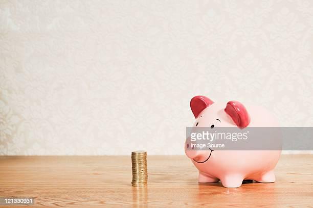 Sparschwein und Stapel von Pfund-Münzen