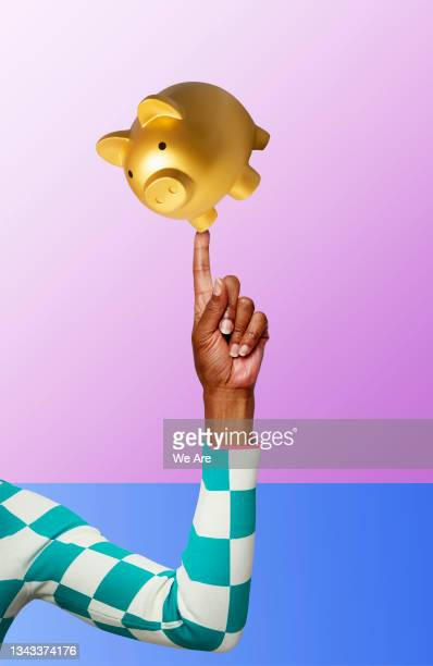 piggy bank balancing on finger - one mature woman only stock pictures, royalty-free photos & images