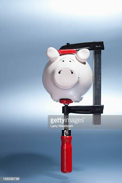 A piggy bank being held in a vise grip suspended in mid-air