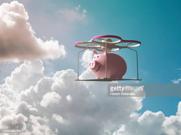 piggy bank flying in the sky on a drone - durability stock photos and pictures