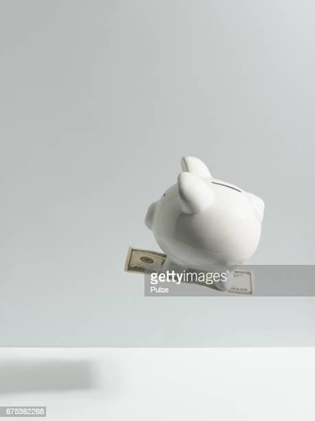 Piggy bank flying on hundred dollars bill.