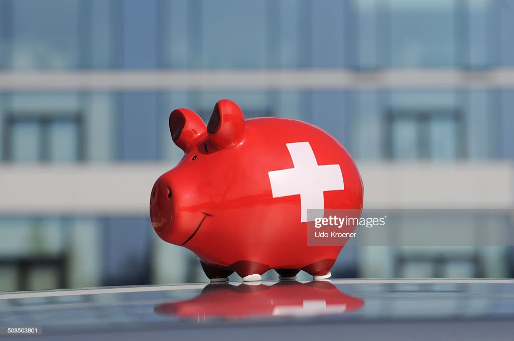 Piggy bank in front of the glass facade of a bank : Stock Photo