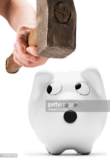piggy bank looking scared as hand comes down with hammer