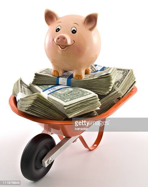 Piggy Bank on a Wheel Barrow Stacked with Money