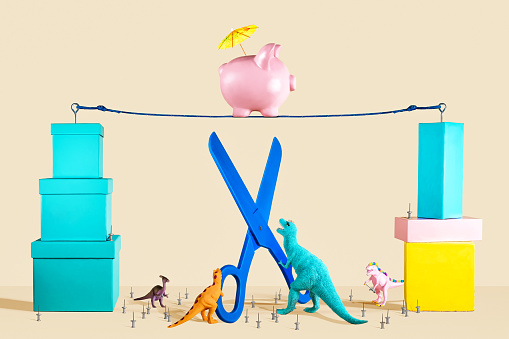 Piggy Bank on Tightrope with Dinosaurs, Thumbtacks and Scissors - gettyimageskorea