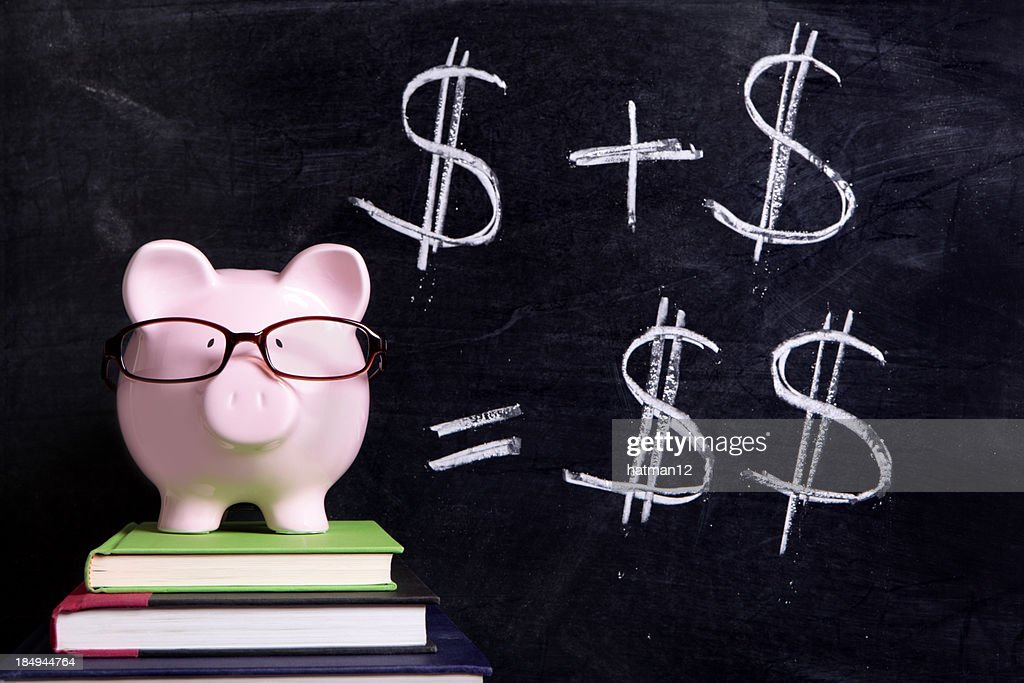 Piggy bank on top of books with money signs on black board : Stock Photo