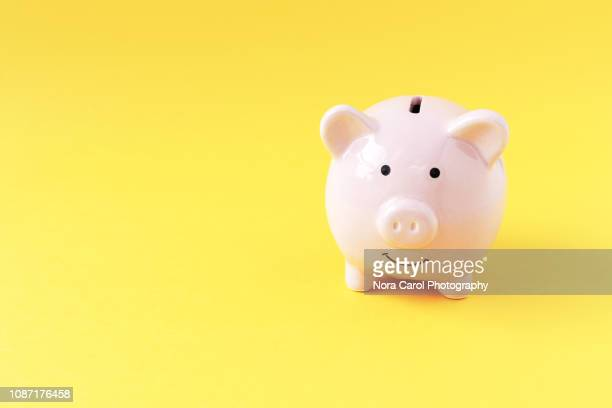 piggy bank on yellow background - ersparnisse stock-fotos und bilder