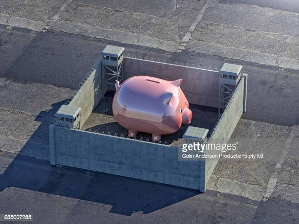 Piggy bank protected by walls with barbed wire