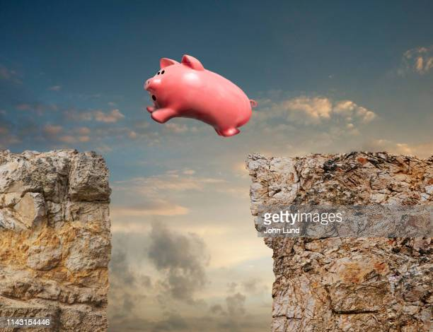 piggy bank taking the leap - cliff stock pictures, royalty-free photos & images
