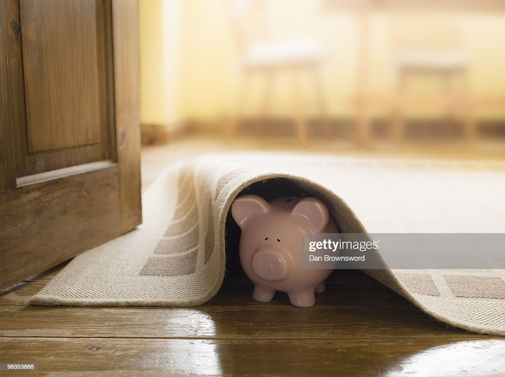 Piggy bank under rug : Stock Photo